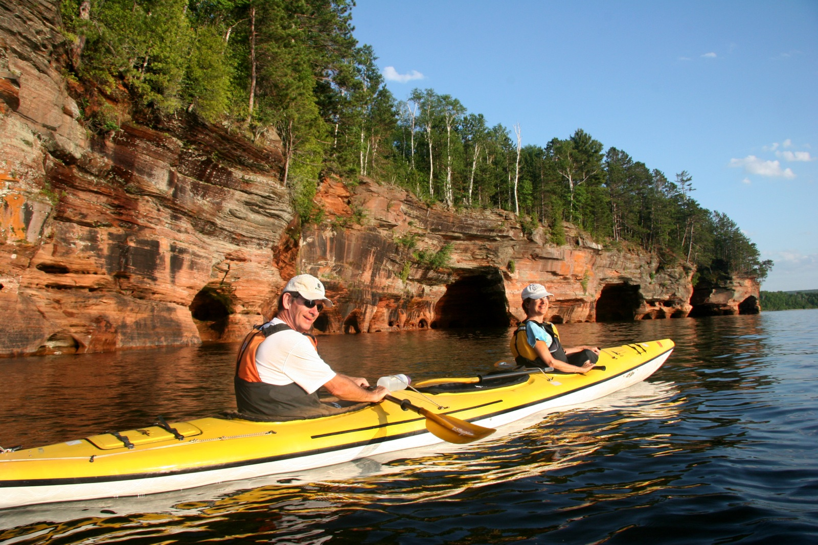 Two kayakers look back at the camera as they paddle a tandem kayak with sandstone cliffs in the background.