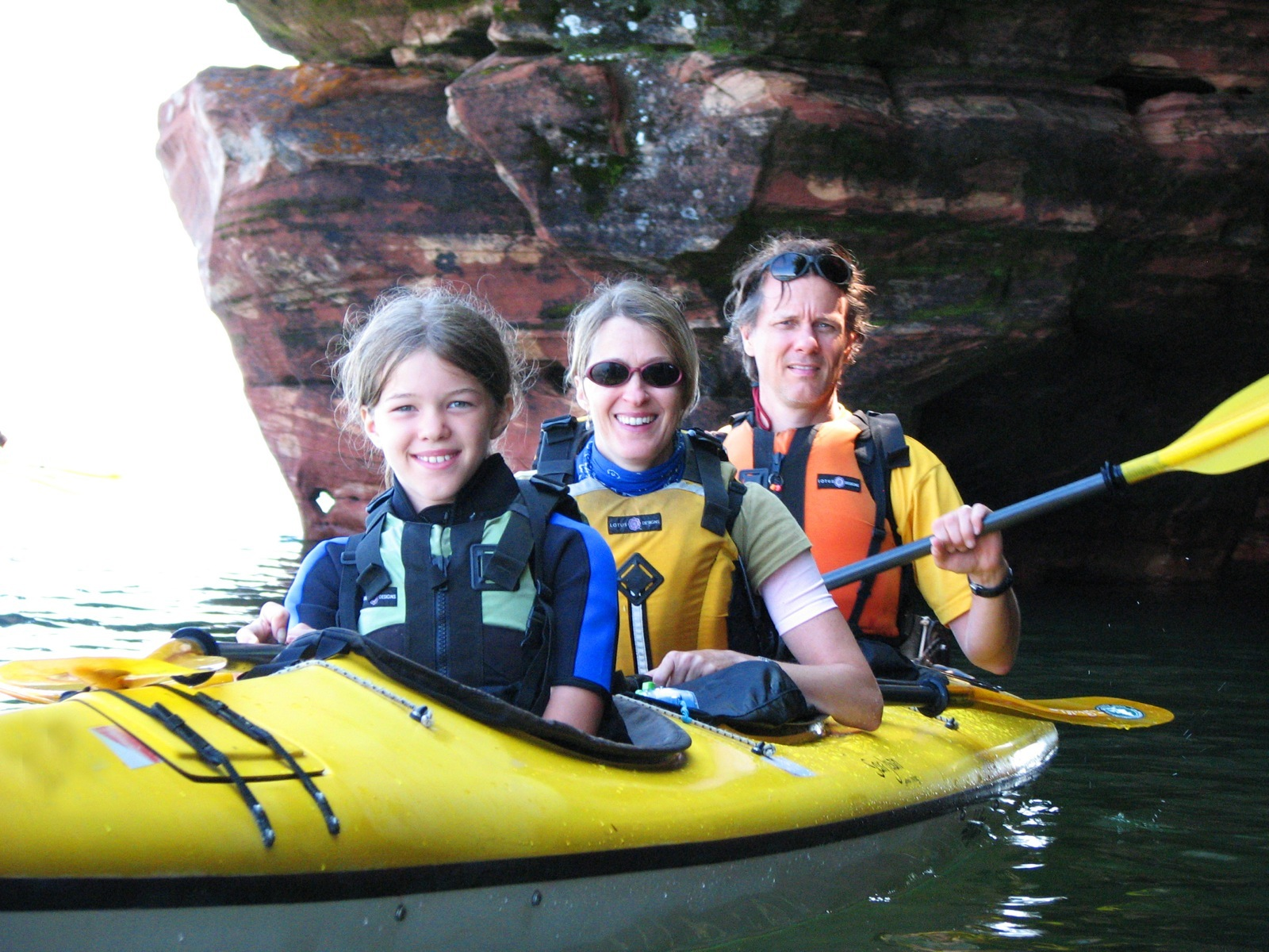 Parents and daughter explore the Mawikwe Bay sea caves in a yellow kayak.