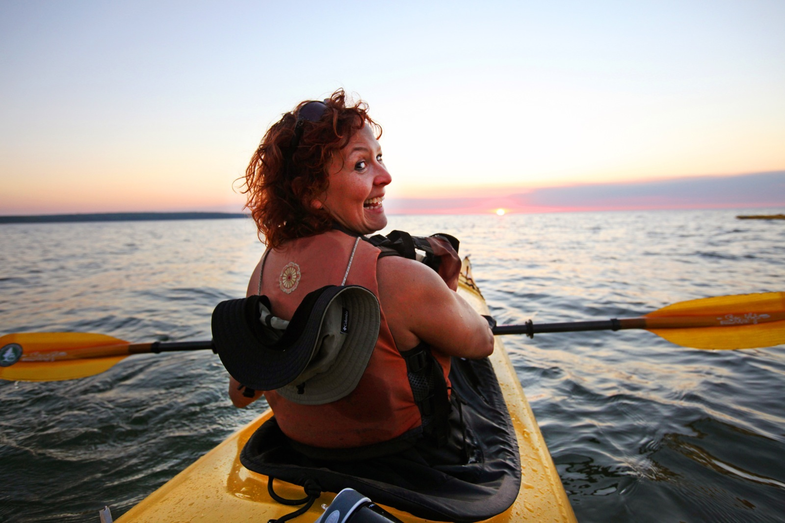 Woman turns around in yellow sea kayak, smiles for camera; sun setting in background.