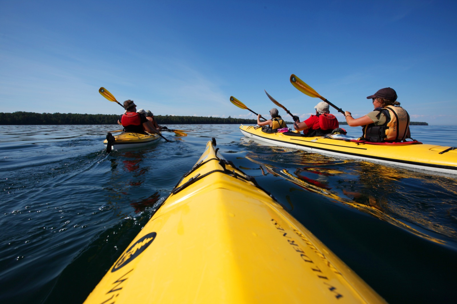 Adults paddling three yellow kayaks on Lake Superior.