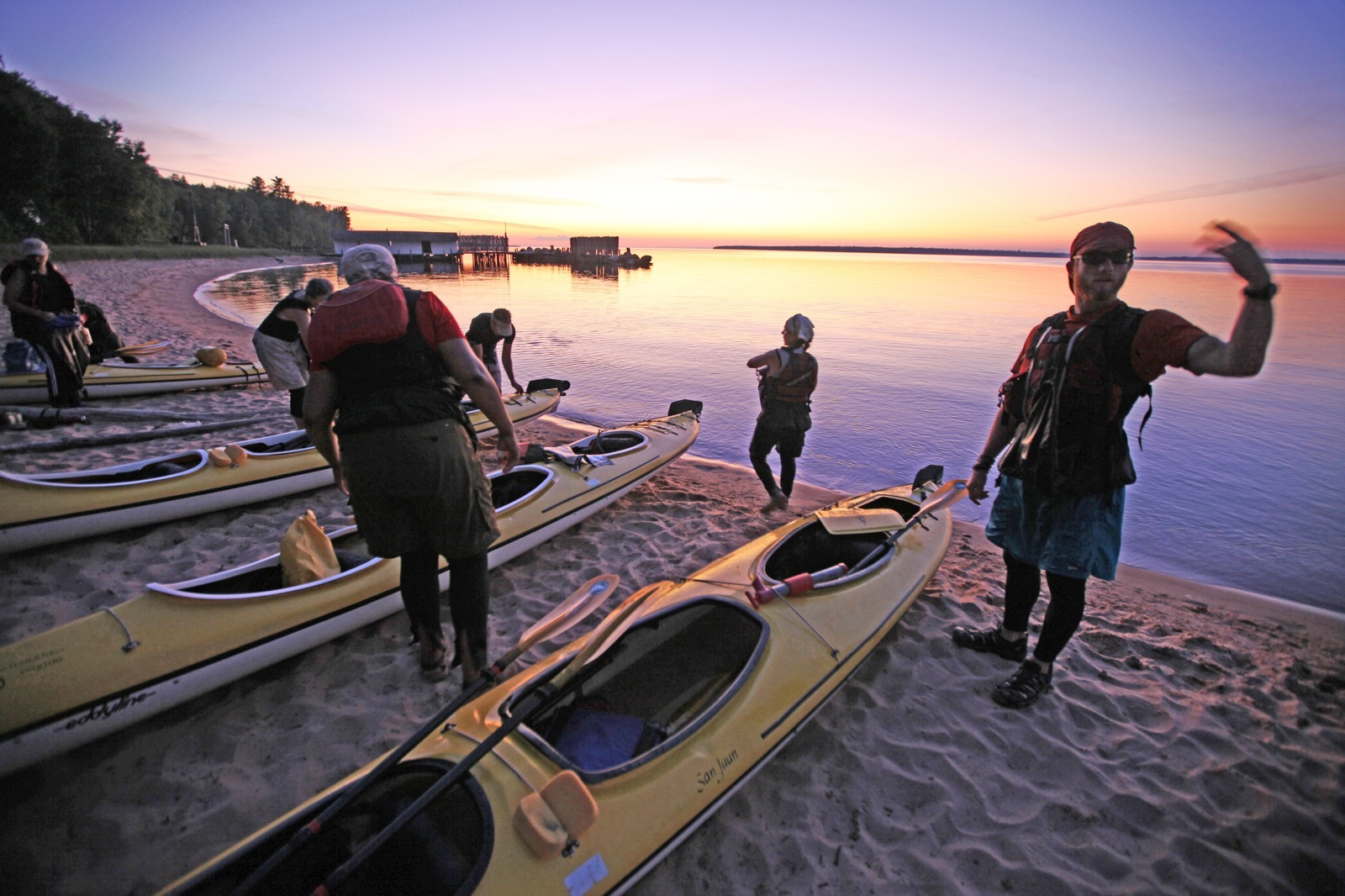 Sea kayakers on the beach of Lake Superior at dusk.