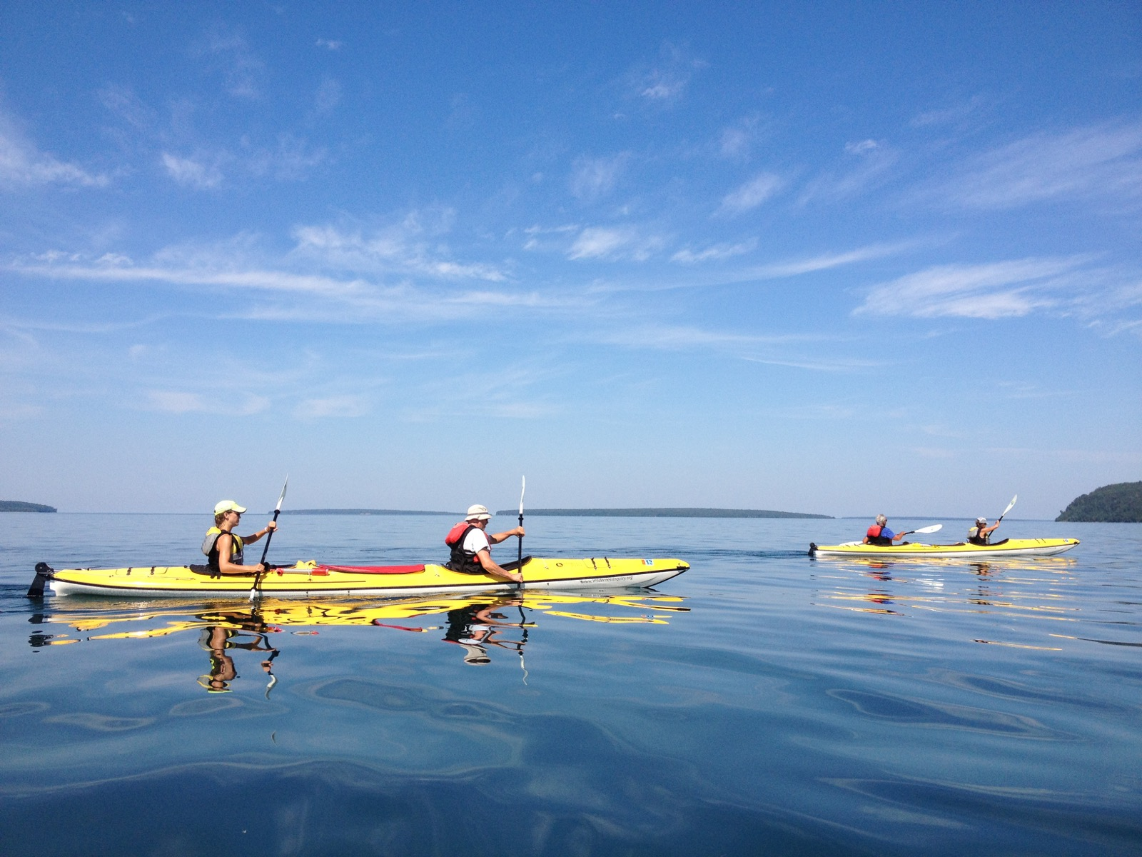 Two yellow kayaks paddle across the glassy surface of Lake Superior on a sunny day.