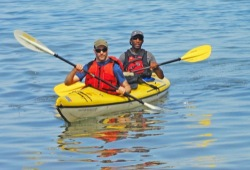 Two men paddle a sea kayak on calm water.