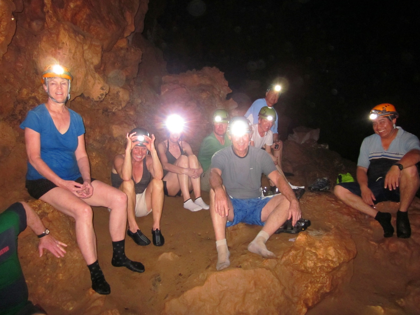 Participants wearing headlamps take a break while caving in Belize.