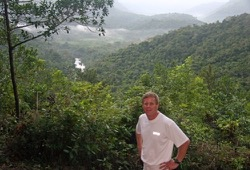 A man poses in front of a lush, green valley near Red Bank in Belize.48