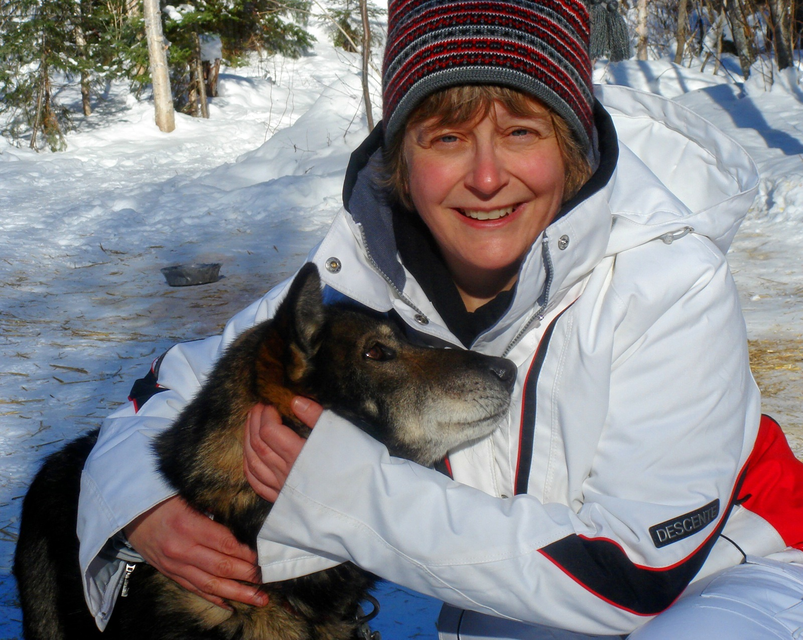 A winter Boundary Waters trip participant cuddles with a sled dog on frozen West Bearskin Lake.