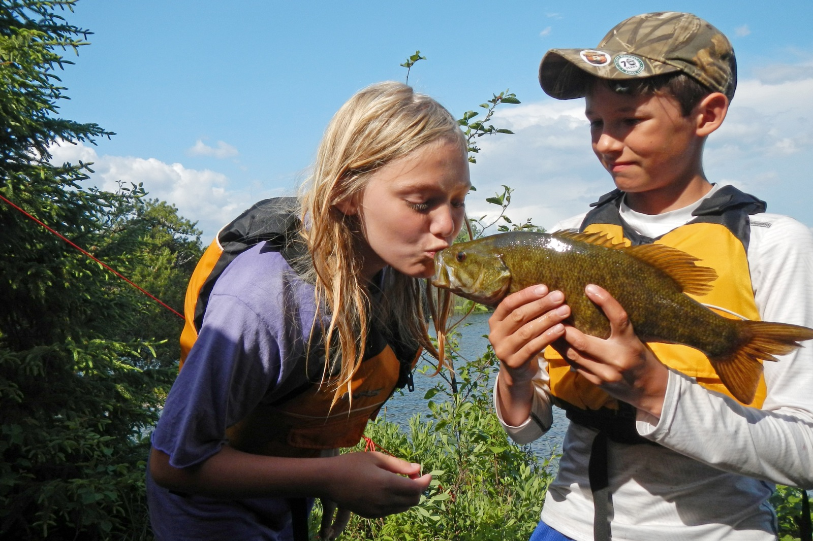 a boy holding a fish while a girl kisses the fish by the lake