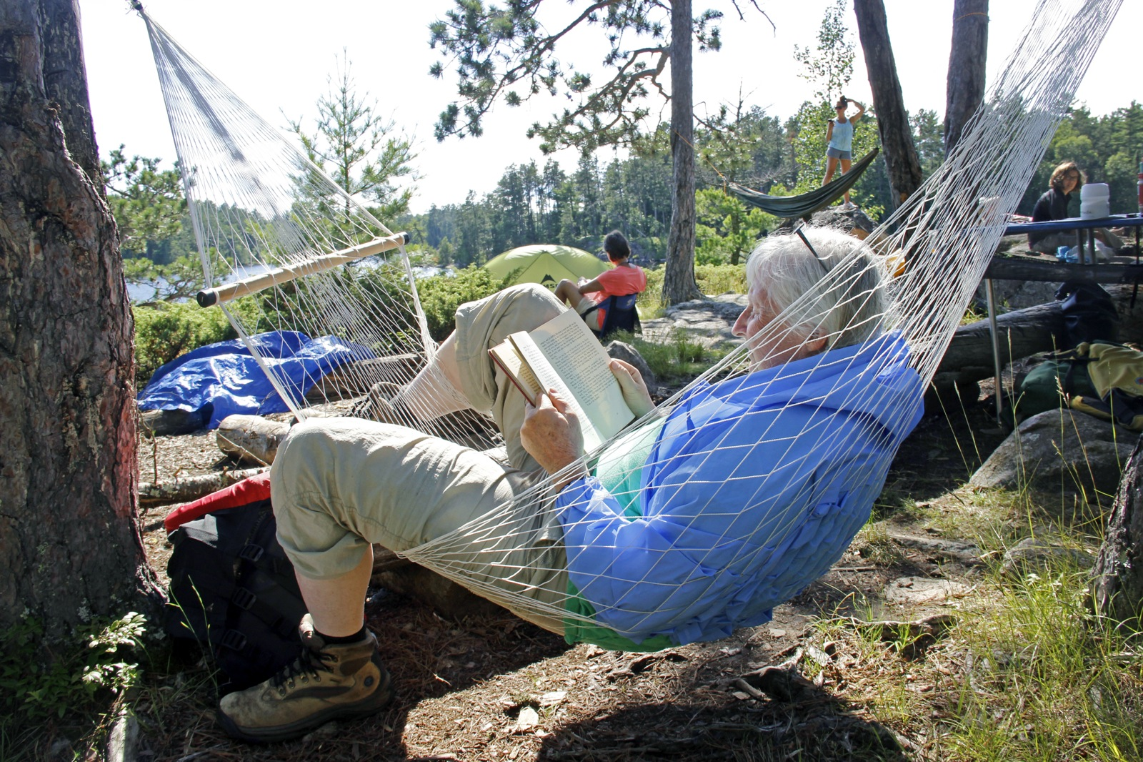 A woman reads a book while sitting in a mesh hammock at her campsite in the Boundary Waters.