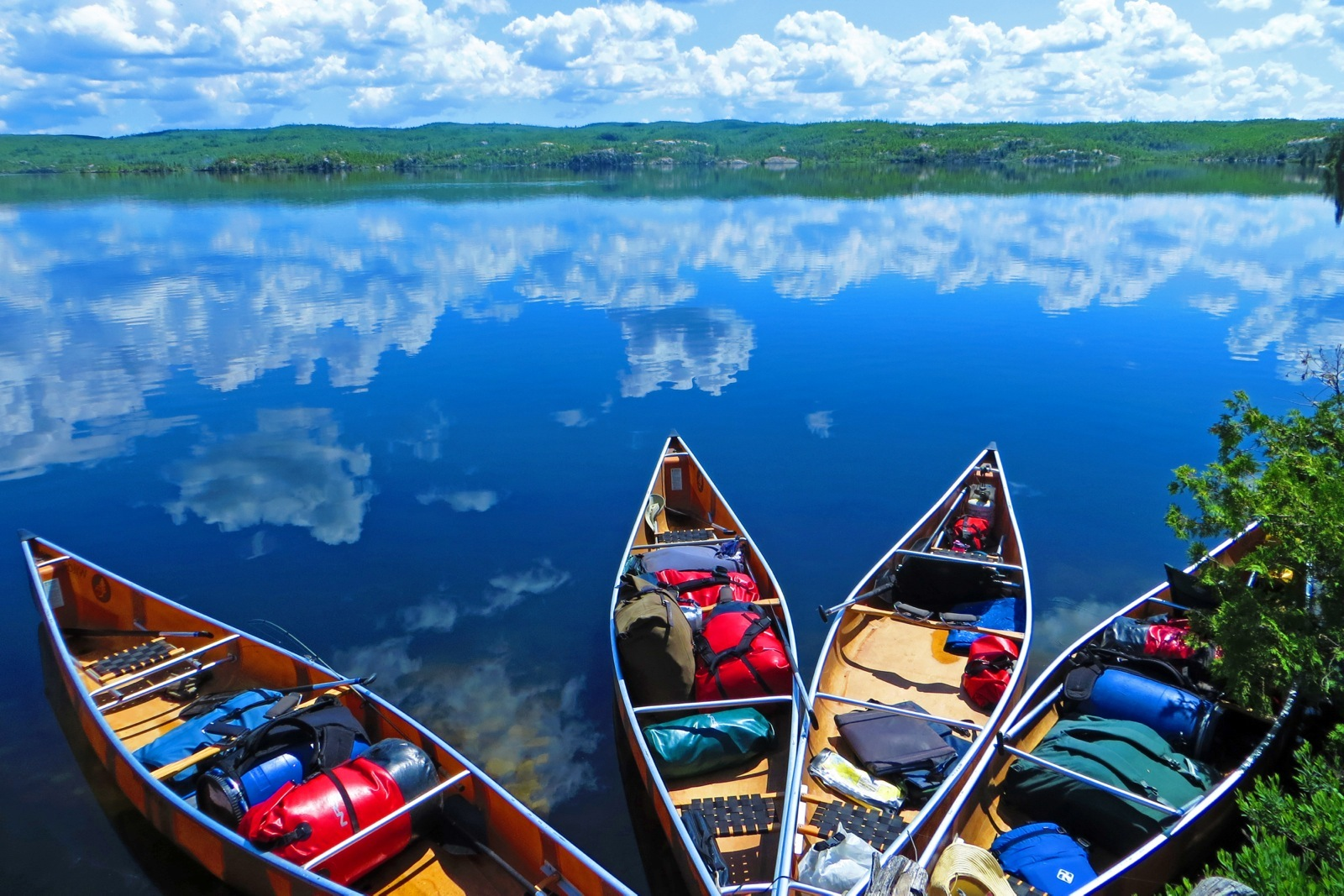 a photo of four canoes with gear packed up on the shore of the BWCA
