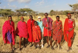 A participant stands with seven Masaai warriors dressed in traditional red Shuka cloths.