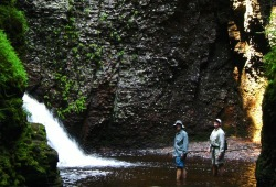 Two participants stand in the water in front of a waterfall on the Kadunce River.