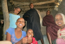 Six Datoga children in their boma smile for the camera.