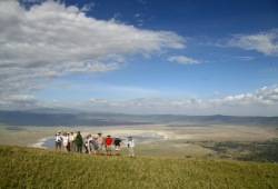 A group of participants stands together for a photo on the edge of Ngorogoro Crater with the plains of the crater and the bright blue sky behind them.