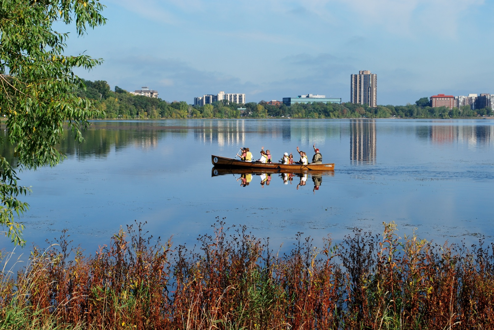 Participants wave from their Voyageur canoe as they paddle across glassy water in the Chain of Lakes.