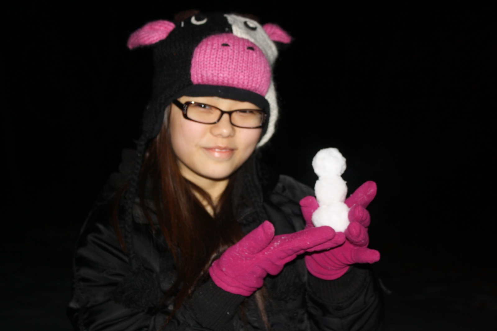 A girl wearing winter clothes smiles while holding a miniature snowman.