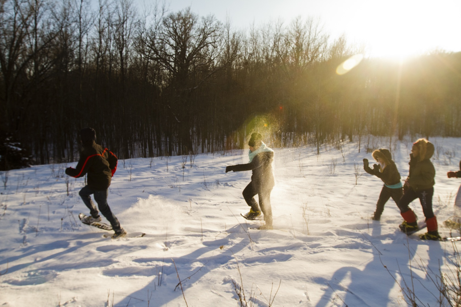 Four young people wearing snowshoes race across a snowy landscape under a sunny sky.
