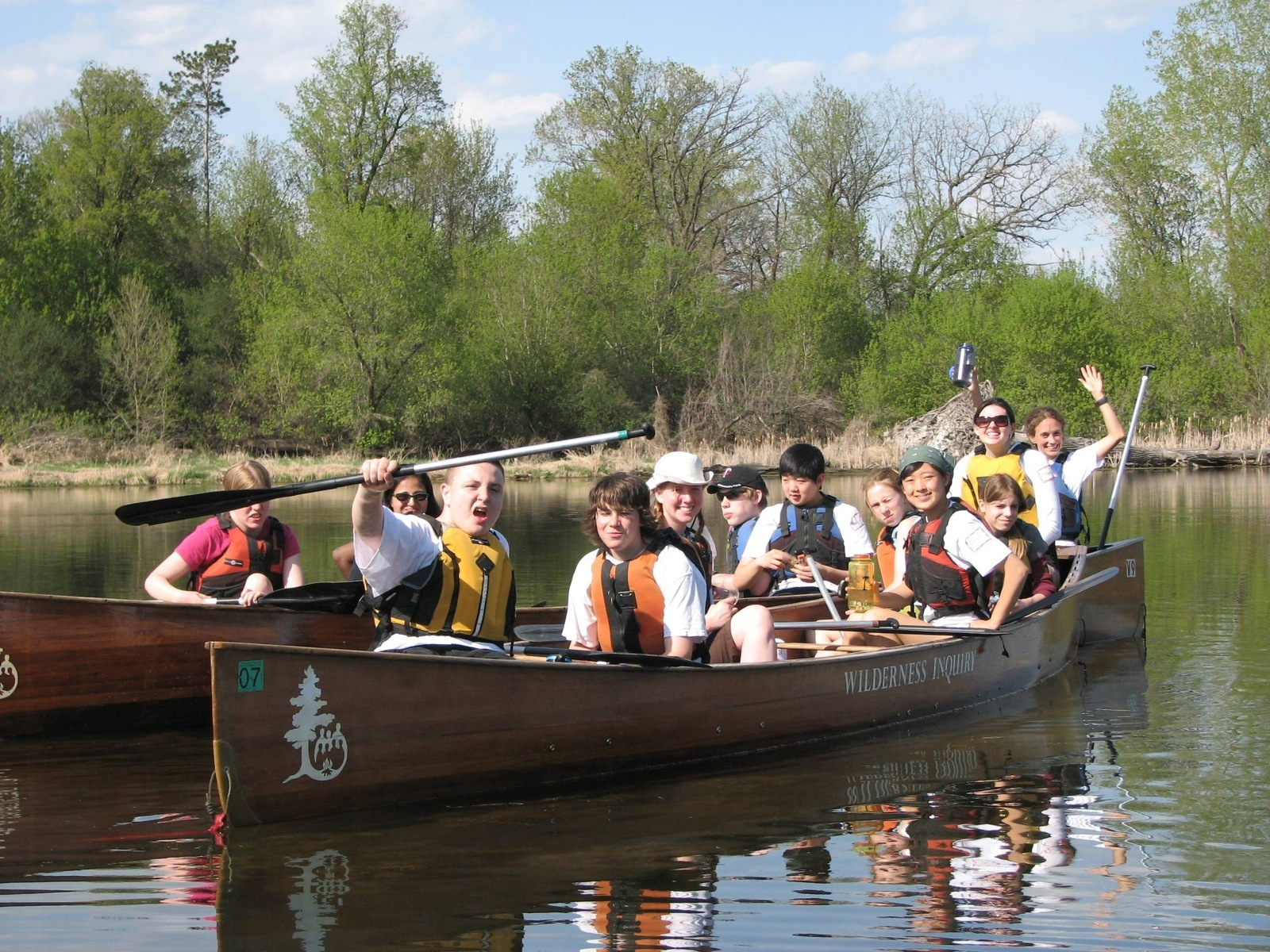 Youth in two Voyageur canoes show off their excitement for paddling with smiles and paddles raised in the air.