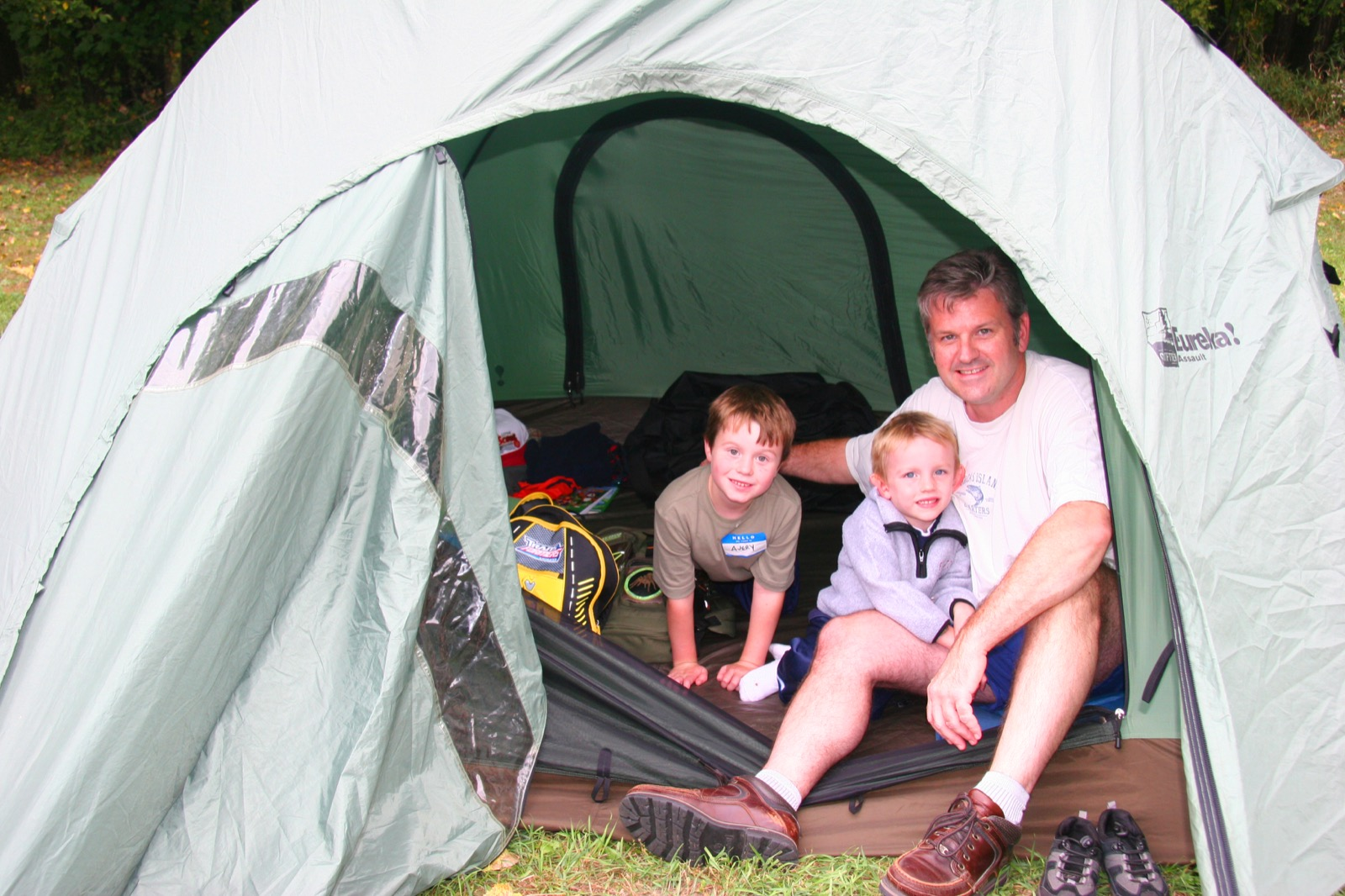 A father and two children peak out of their tent on a Family Overnight at Fort Snelling State Park.