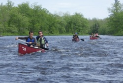 Participant with yellow lifejacket gives big smile to camera during Chain of Lakes canoe trip.
