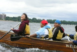 Participants smile at the camera as they paddle in the bow of a Voyageur canoe on the Chain of Lakes in Minneapolis.