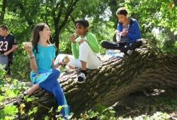 Three youth sit on a downed tree trunk while enjoying an outdoors lunch.