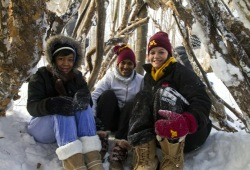 Three young women smile while huddling under a shelter they made of sticks during a snowy winter adventure.