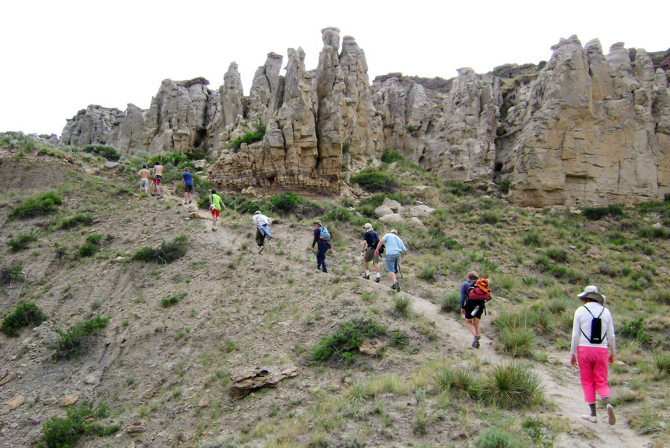 A group hikes single file past towering rock formations to see the Hole-in-the-Wall, one of the Missouri's most iconic rock formations.