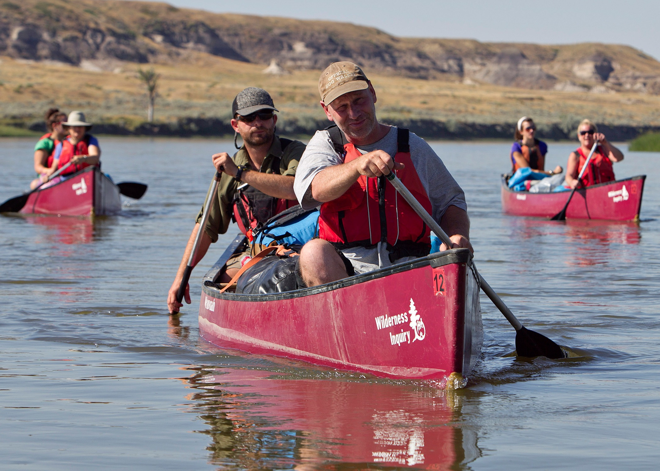 Three red Wilderness Inquiry tandem canoes paddle the Missouri River with cliffs in the background.