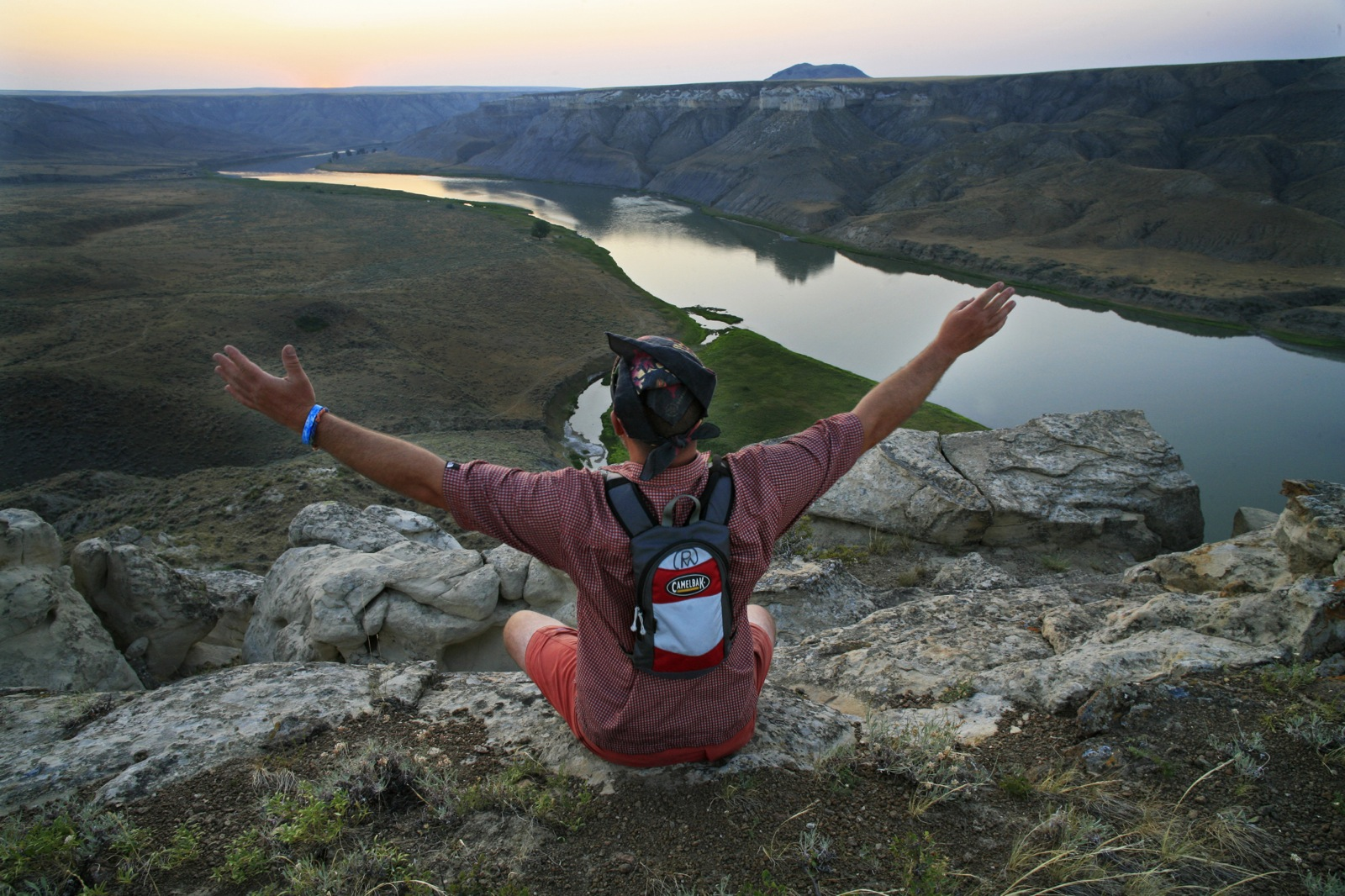 A participant sits high above Montana's Missouri River at sunset and lifts his arms in delight.