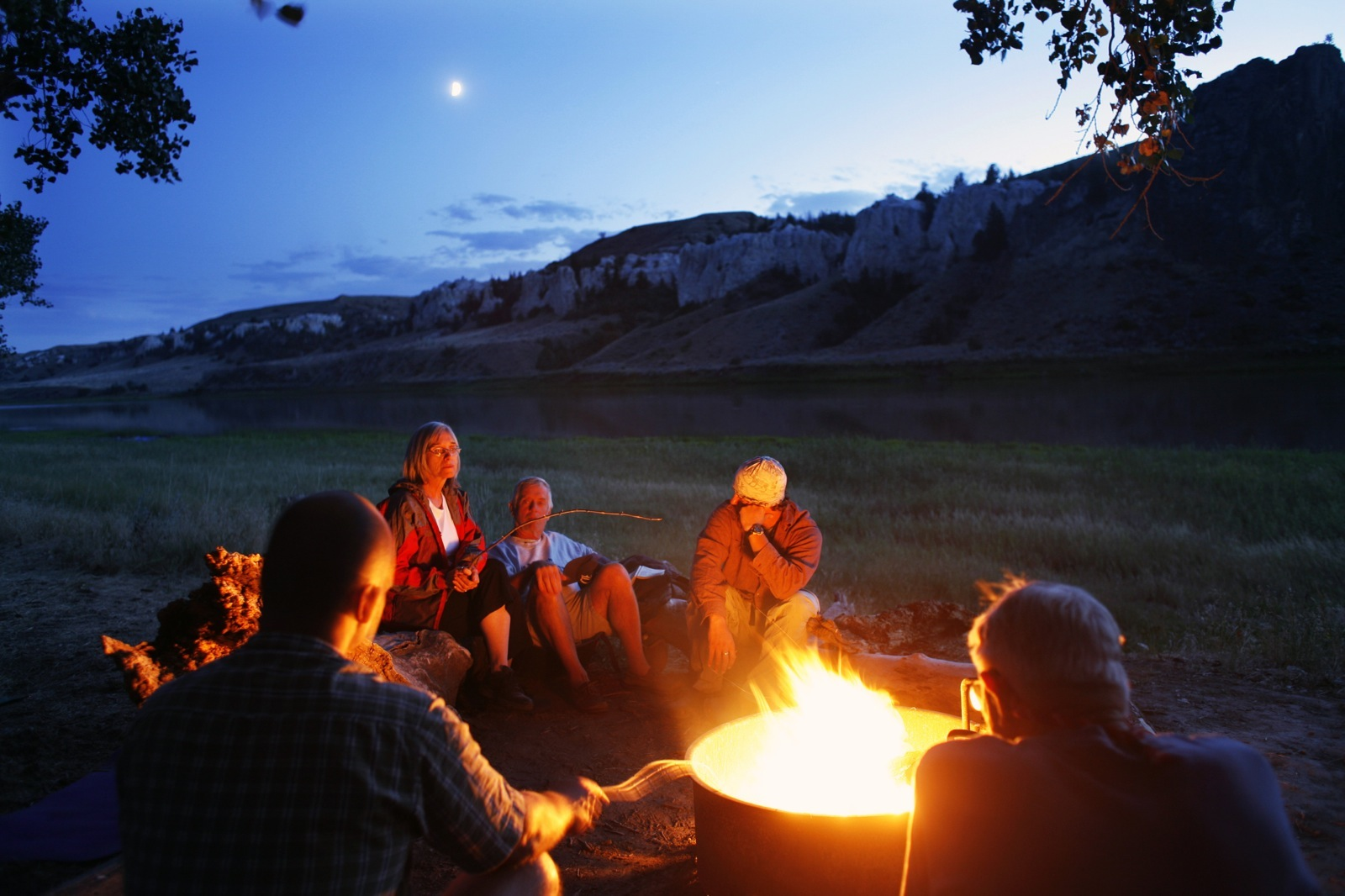 The Wilderness Inquiry group gathers around a campfire at dusk near the site of a stop on the Lewis and Clark expedition.
