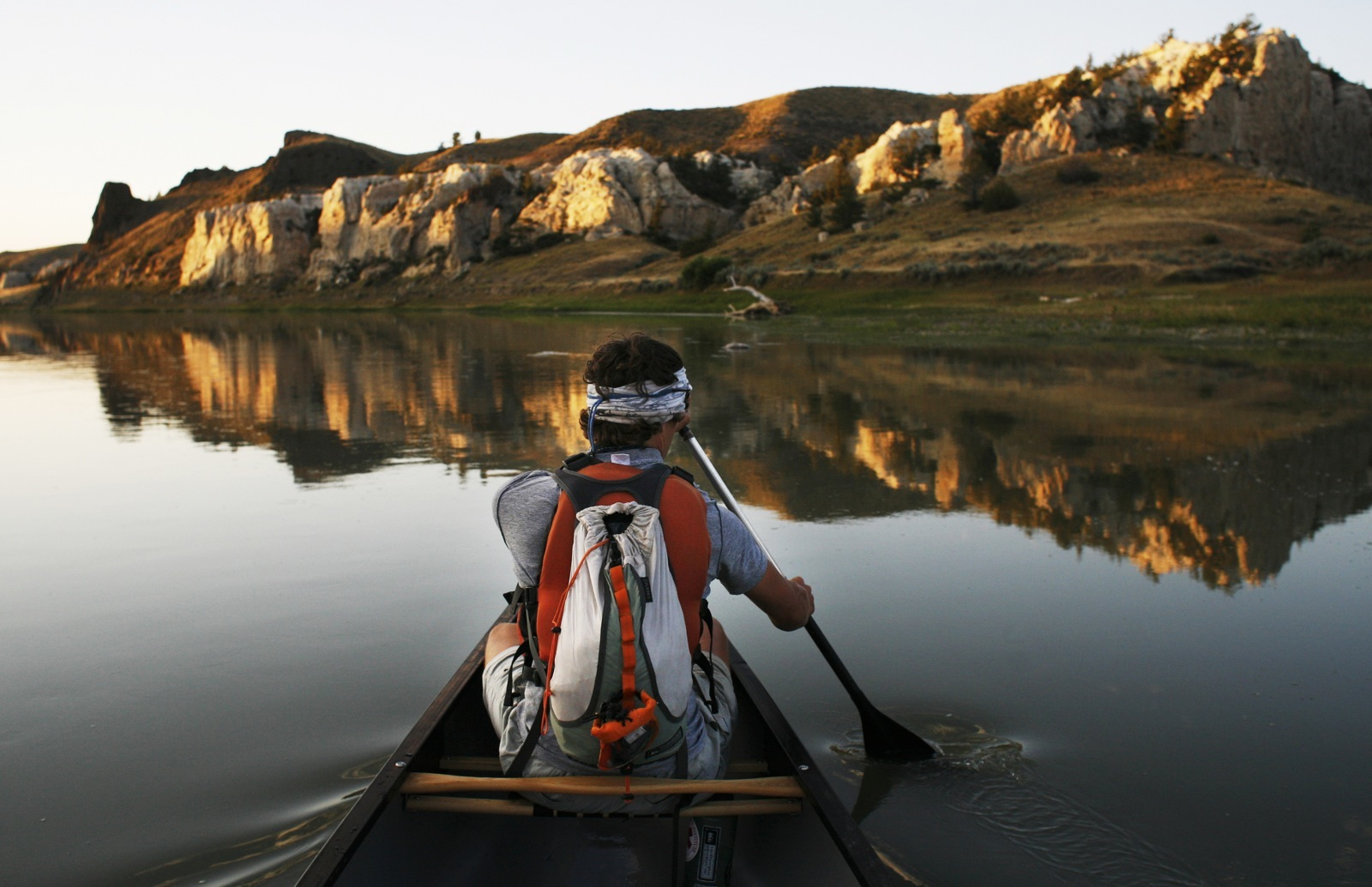 The bow paddler in a tandem canoe aims towards the White Cliffs of the Missouri River, which are reflected in the river's glassy water.