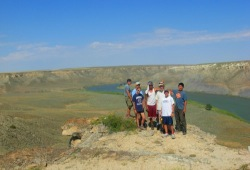Under vibrant blue skies, a group of teenagers gathers at the top of a canyon for a great view of the Missouri River.