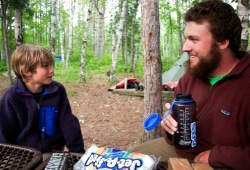 A boy and a Wilderness Inquiry guide have a conversation while sitting at a picnic table at their campsite.