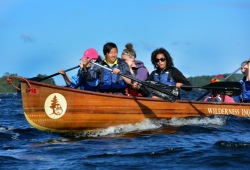 A group of young adults paddles in the bow of a Voyageur canoe as it breaks through the dark blue waves.