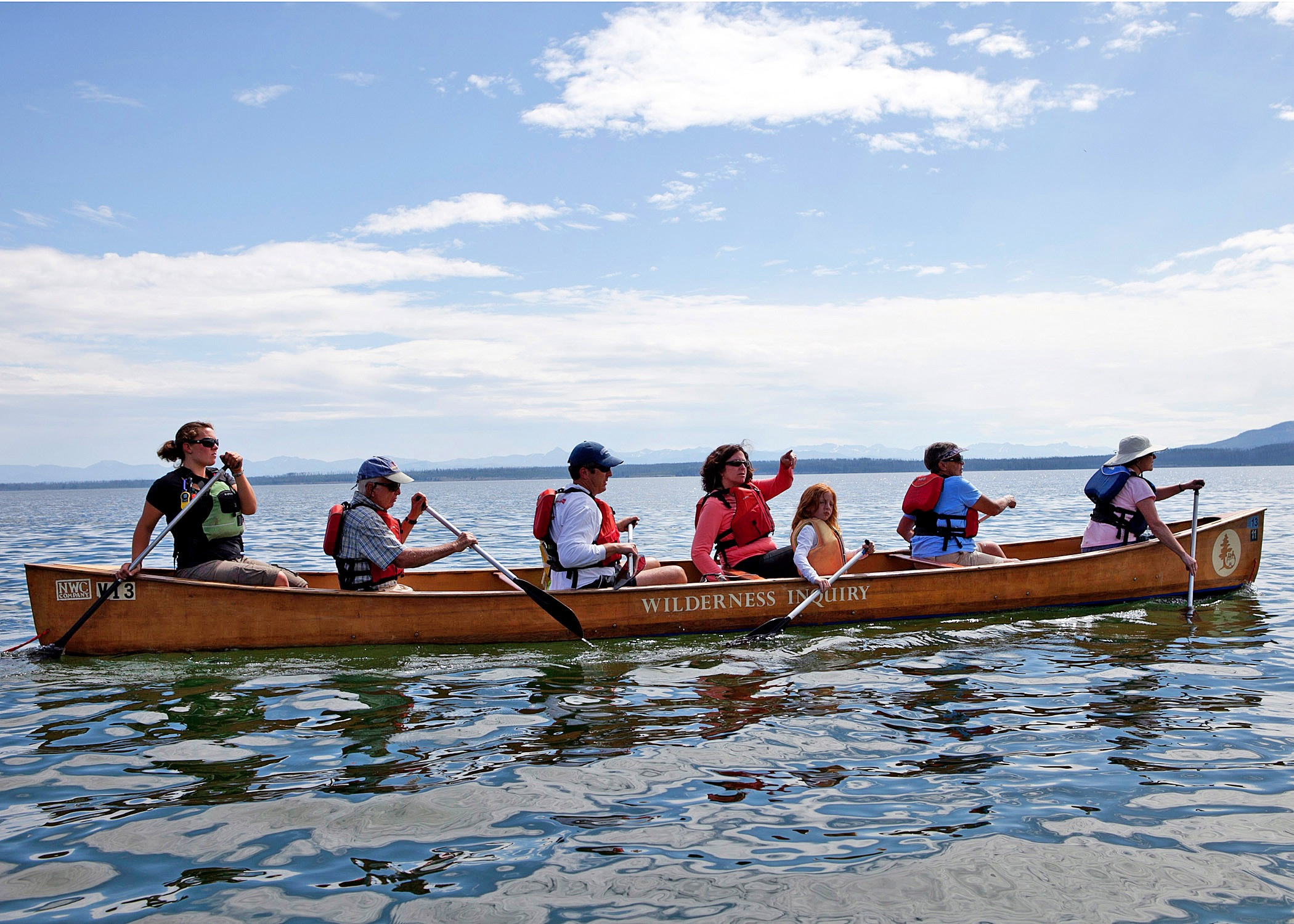 a group of 7 canoes on Yellowstone Lake while enjoying the sunny day