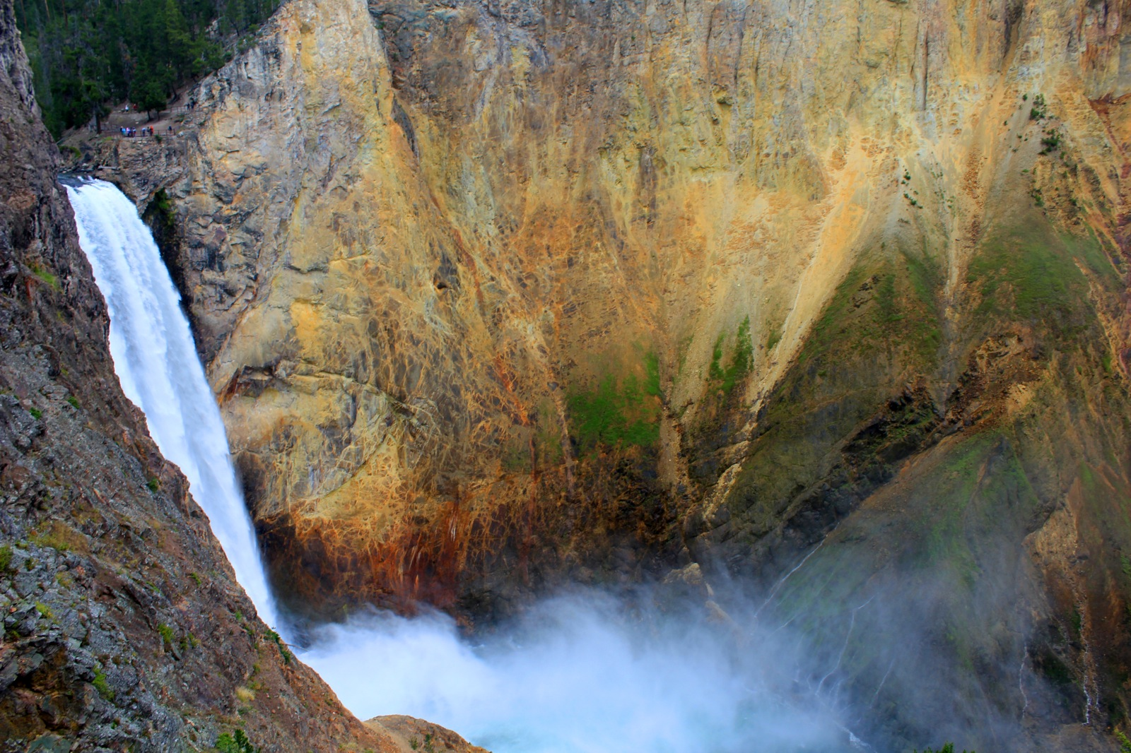 Mist rises up from an enormous waterfall cascading into a giant, deep canyon.