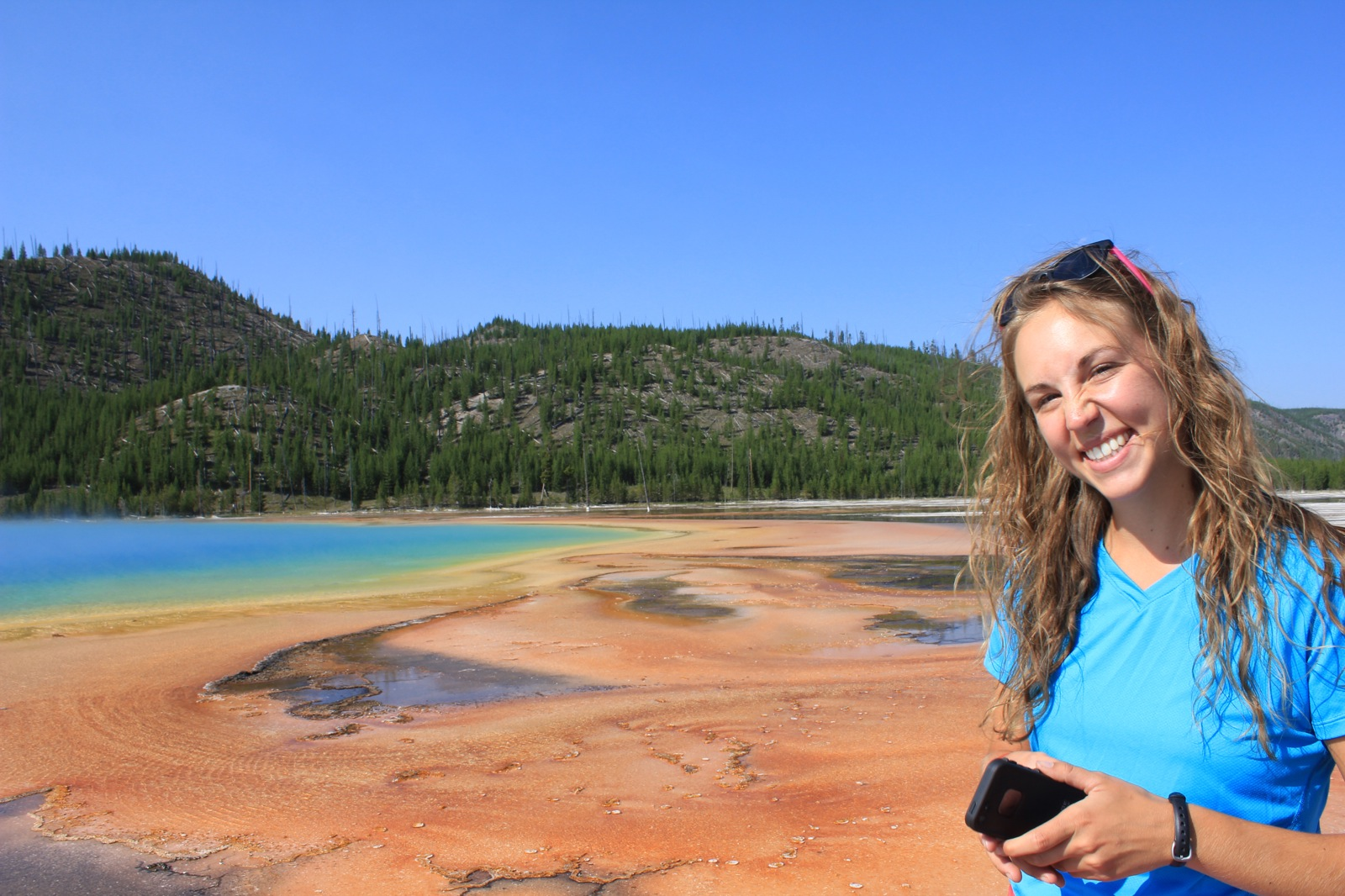 A woman poses in front of the blues, greens, yellows, and oranges of Grand Prismatic Spring, the park's largest hot spring.