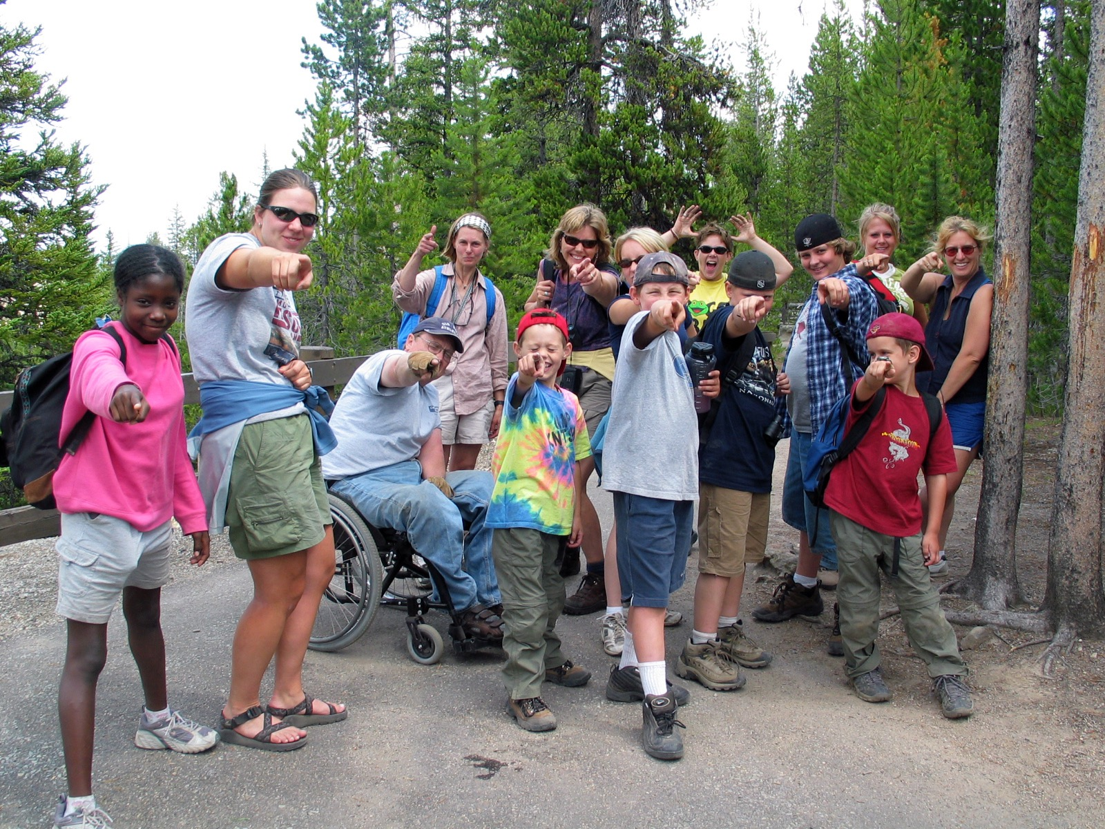 The group points towards the camera and poses for a picture near Mount Washburn.