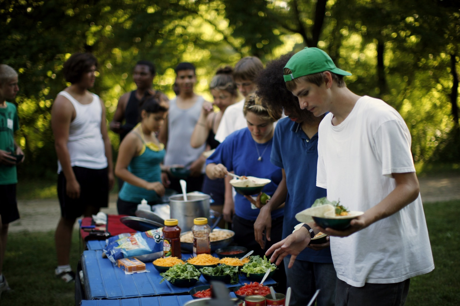 At their campsite, a group of young people lines up at a buffet of burrito ingredients to put together their dinner.