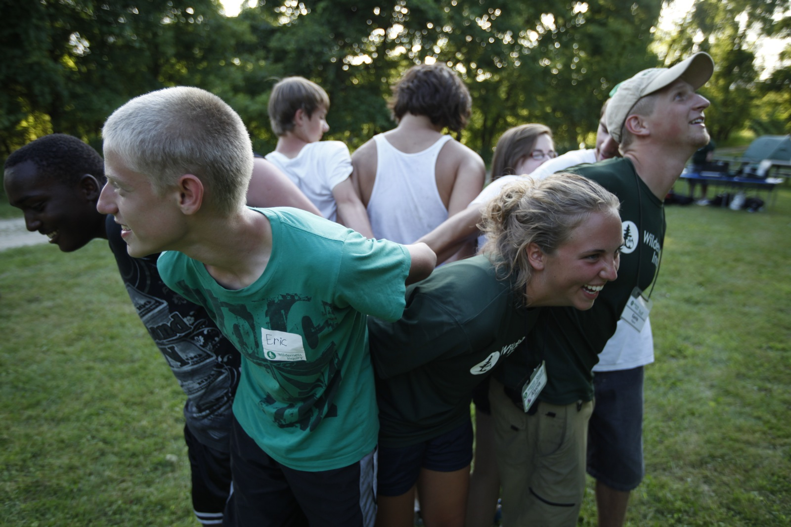 "Nine young people stand in a tight circle facing outwards with their arms intermingled as they work together on a teambuilding initiative called ""Human Knot."""
