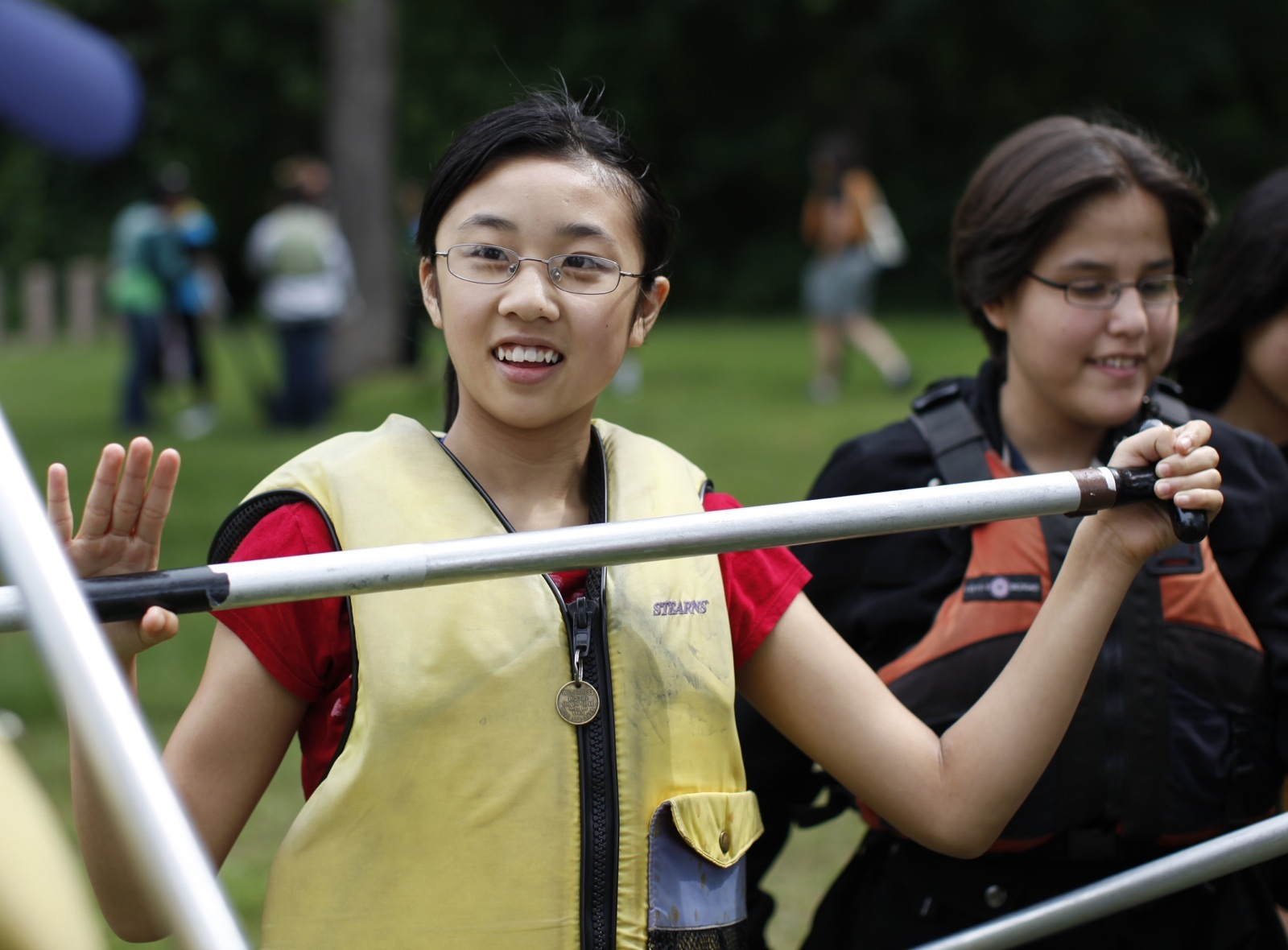 A girl in a life jacket looks towards her guide as she practices holding a canoe paddle.