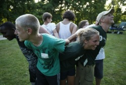 """Nine young people stand in a tight circle facing outwards with their arms intermingled as they work together on a teambuilding initiative called """"Human Knot."""""""