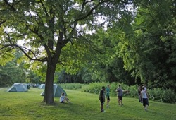 A group of teenagers plays a game near their tents at a campsite surrounded by lush green grass and trees.