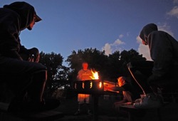 Participants sit around a campfire under a clear, deep blue sky at dusk.