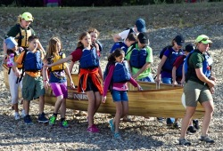 A group of youth and two Wilderness Inquiry staff works together to carry a 24-foot Voyageur canoe down a pebble beach.