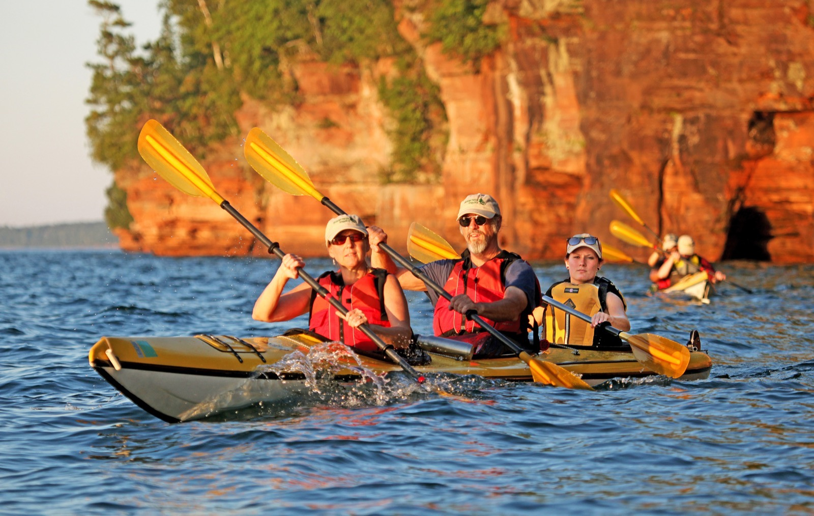Three kayakers in a yellow kayak paddle on the lake with red sandstone cliffs in the background.
