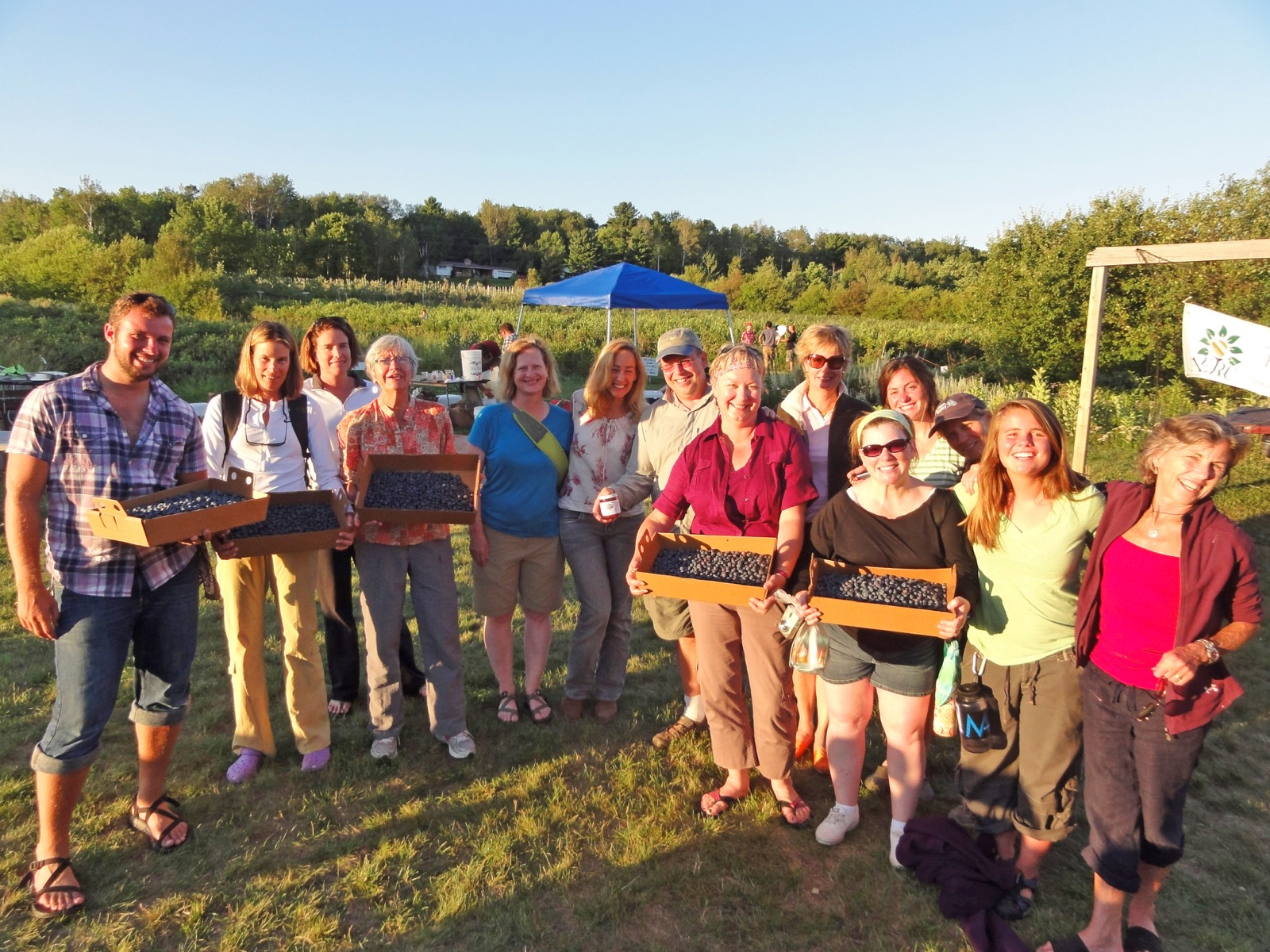 A group poses for the camera while holding many boxes of blueberries.