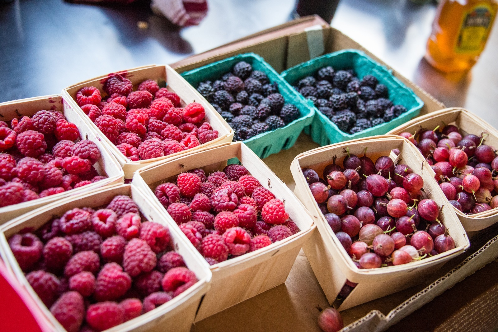 Eight boxes of fresh raspberries and blueberries.