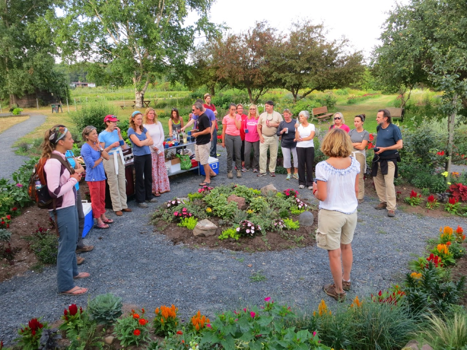 A woman addressing a group of adults in a garden.