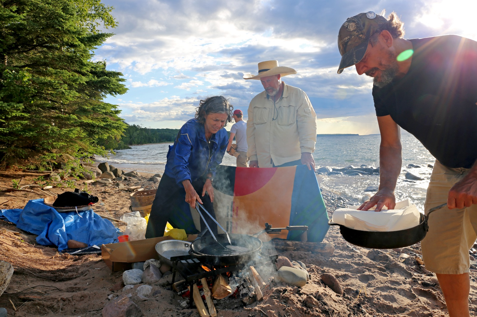 Man holding frying pan and woman cooking over a fire on the beach.